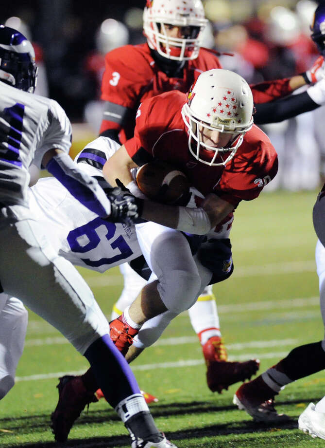 At right, Greenwich running back Thomas Rippa (# 30) gets past a diving Malik Dawkins (# 67) of Westhill during the high school football game between Greenwich High School and Westhill High School at Greenwich, Friday, Nov. 8, 2013. Photo: Bob Luckey / Greenwich Time