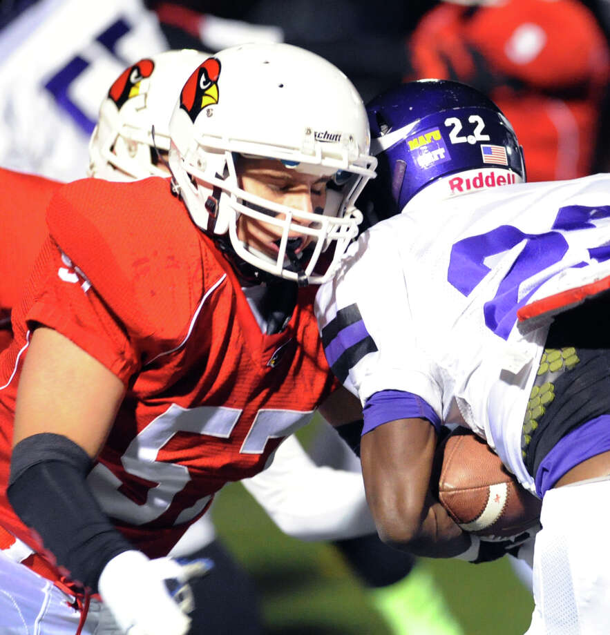 At left, Dom Colasacco (# 57) of Greenwich tackles Westhill running back Tyreece Mitchell (# 22) during the High school football game between Greenwich High School and Westhill High School at Greenwich, Friday, Nov. 8, 2013. Photo: Bob Luckey / Greenwich Time