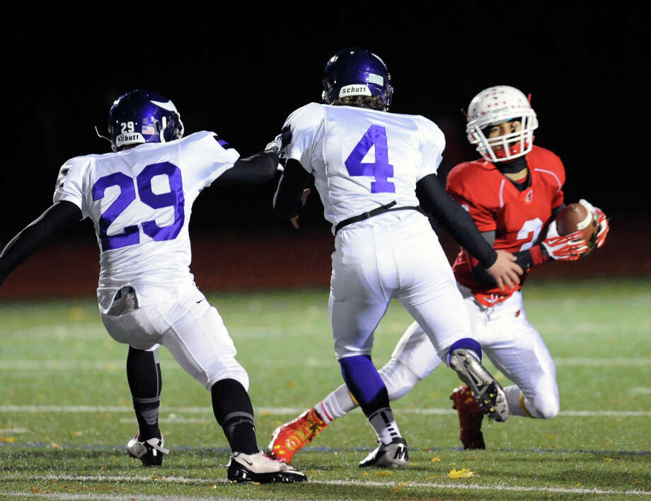 At right, Austin Longi (#3) of Greenwich puts a move on Westhill defenders Yovanni Goris (# 29) and Jack Cebo (# 4) during the first quarter of the high school football game between Greenwich High School and Westhill High School at Greenwich, Friday, Nov. 8, 2013. Photo: Bob Luckey / Greenwich Time