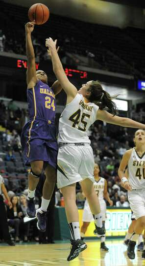 UAlbany's Keyontae Williams goes up for a basket guarded by Siena's Meghan Donohue during a basketba