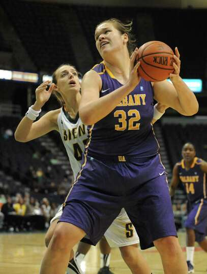 UAlbany's Megan Craig drives to the hoop as she is guarded by Siena's Meghan Donohue during a basket