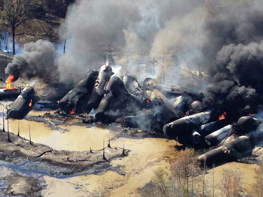 A tanker train carrying crude oil burns after derailing in western Alabama.  The train exploded, sending flames and smoke into the air and forcing a family to leave its home. Photo: Bill Castle / ABC 33/40 / Associated Press