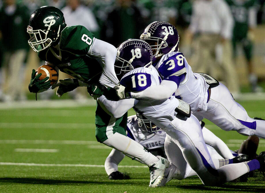Stratford High School's Terrance Peters holds onto the ball as he's brought down by Ridge Point High School safety Tyler Turner, center, and linebacker Stevan Blaylock, right, during the third quarter of a football game at Darrell Tully Stadium, Friday, Nov. 8, 2013, in Houston. Stratford won 17-3. Photo: Cody Duty, Houston Chronicle / © 2013 Houston Chronicle