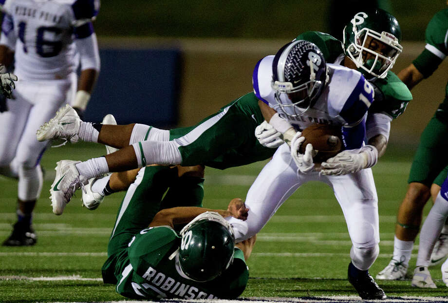 Ridge Point High School's Jax Biggers holds onto the ball as he's tackled by Stratford High School's Ragan Robinson, left, and Brice Stevenson, right, during the fourth quarter of a football game at Darrell Tully Stadium, Friday, Nov. 8, 2013, in Houston. Stratford won 17-3. Photo: Cody Duty, Houston Chronicle / © 2013 Houston Chronicle