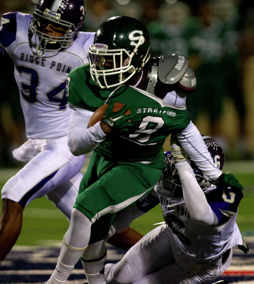 Stratford High School's Terrance Peters holds onto the ball as he's brought down by Ridge Point High School's Cameron Townsend, left, and Blake Wesley, right, during the third quarter of a football game at Darrell Tully Stadium, Friday, Nov. 8, 2013, in Houston. Stratford won 17-3. Photo: Cody Duty, Houston Chronicle / © 2013 Houston Chronicle