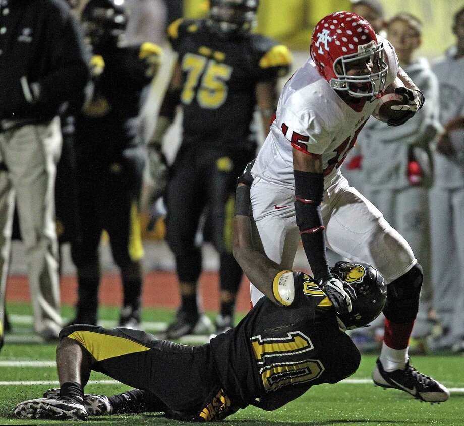 Alief Taylor's Romello Brooker breaks the tackle of Hasstings' Devijea Kiser Carter during the first half of a high school football game, Friday, November 8, 2013 at Crump Stadium in Houston. Photo: Eric Christian Smith, For The Chronicle