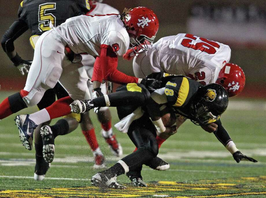 Hastings' D'angelo Collier (18) is tackled by Alief Taylor's Landell Johnson, left, and Kenneth Robinson during the first half of a high school football game, Friday, November 8, 2013 at Crump Stadium in Houston. Photo: Eric Christian Smith, For The Chronicle