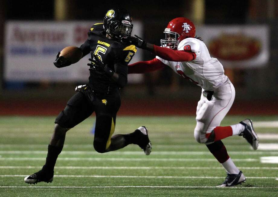 Hastings' Joshua Wiggins (5) escapes the tackle of Alief Taylor's Landell Johnson during the first half of a high school football game, Friday, November 8, 2013 at Crump Stadium in Houston. Photo: Eric Christian Smith, For The Chronicle