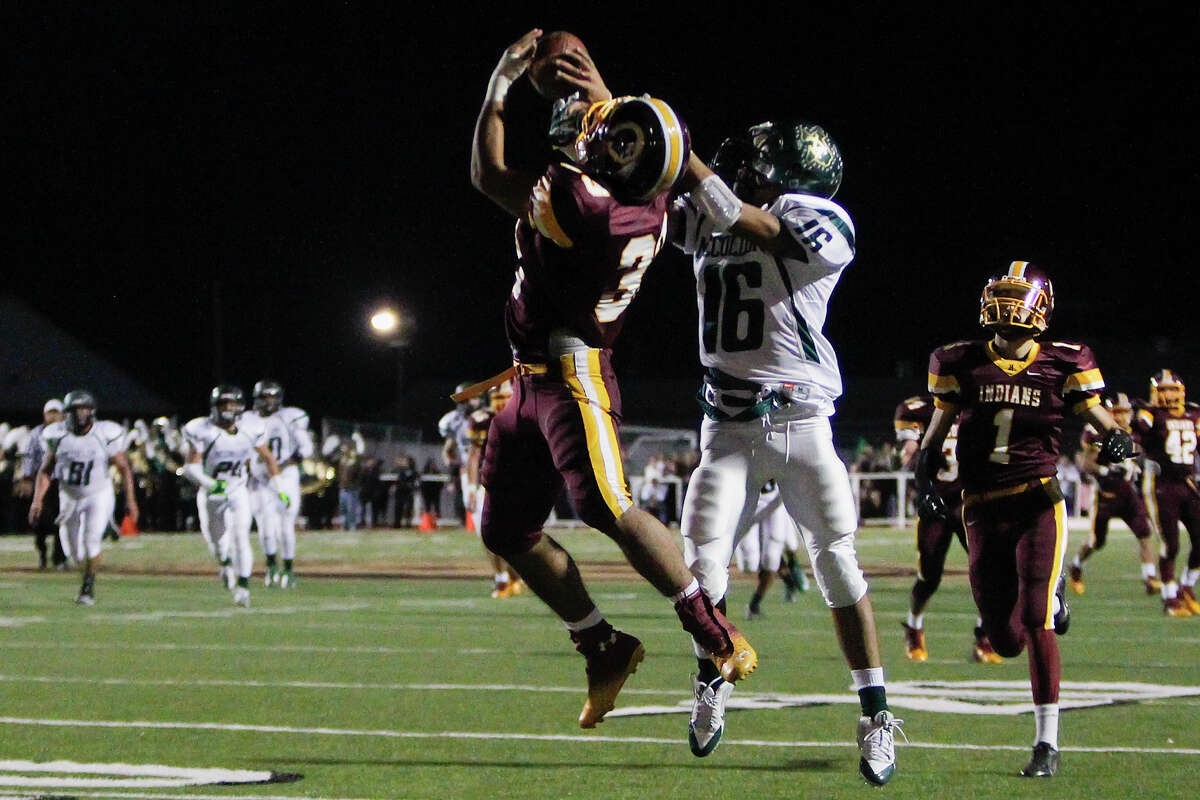 Harlandale's Vicgtory Flores (center left) breaks up a pass intended for McCollum's Justin Villanueva during the first half of the 50th annual Frontier Bowl between Harlandale and McCollum at Harlandale Memorial Stadium on Friday, Nov. 8, 2013. MARVIN PFEIFFER/ mpfeiffer@express-news.net
