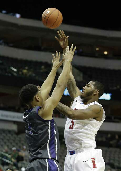 SMU forward Markus Kennedy shoots over TCU's Brandon Parrish in the first half. The Mustangs won 69-61 in the season opener for both teams. Photo: LM Otero / Associated Press