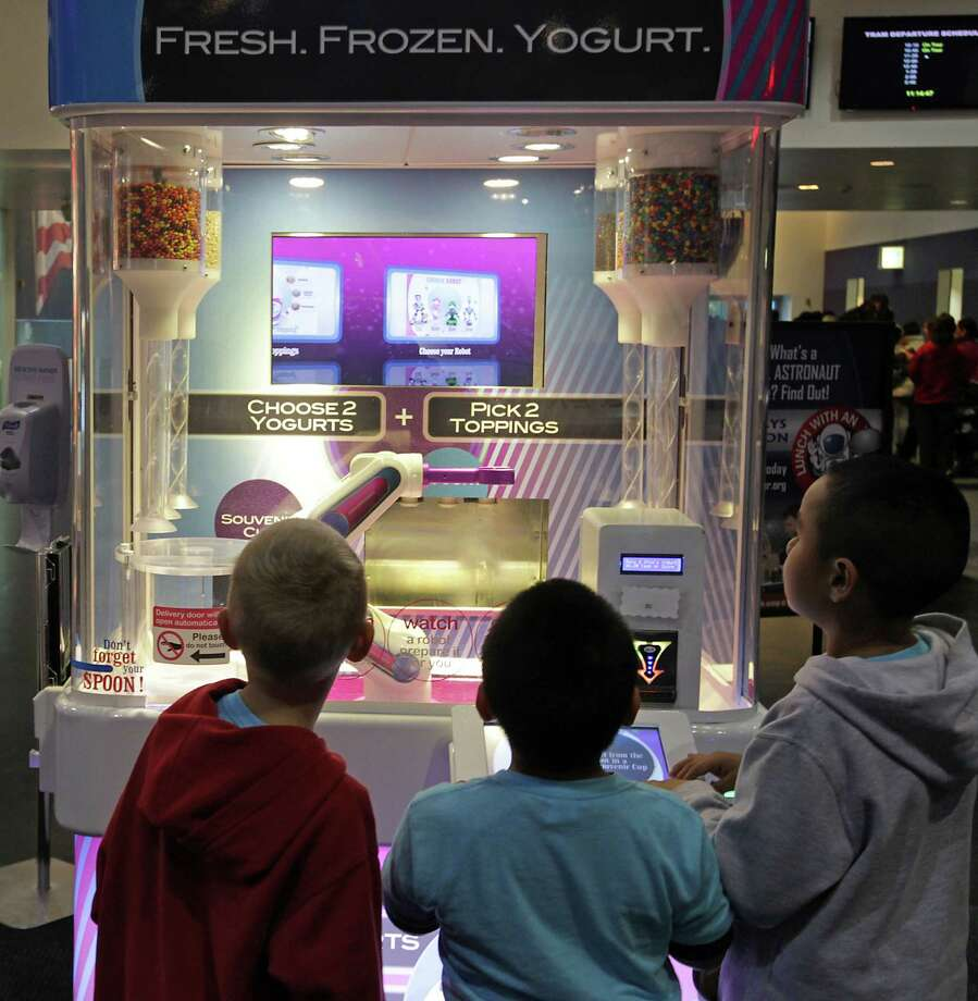 Young visitors look over the robotic frozen yogurt kiosk at Space Center Houston. Building a treat takes about 45 seconds. Photo: James Nielsen, Staff / © 2013  Houston Chronicle
