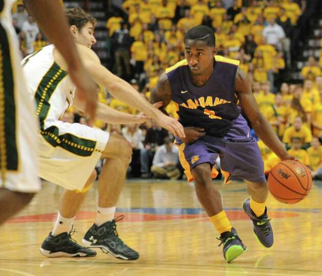Guarded by Siena's Rob Poole, UAlbany's DJ Evans takes the ball down the court during a basketball g