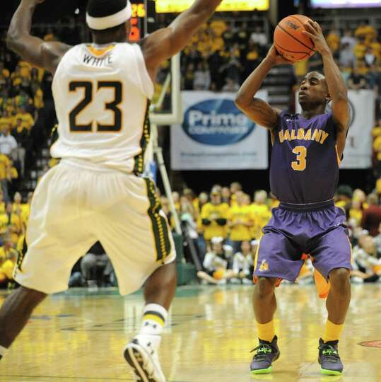 Guarded by Siena's Maurice White, UAlbany's DJ Evans takes a shot during a basketball game at the Ti