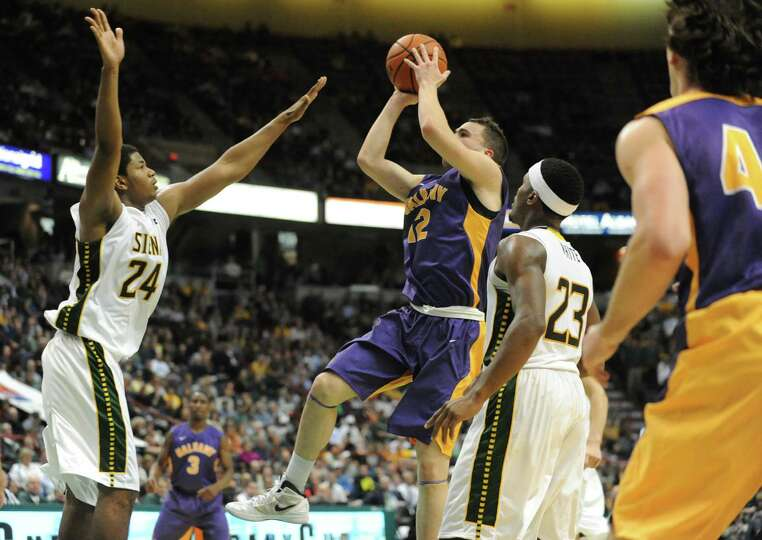 Guarded by Siena's Lavon Long, UAlbany's Peter Hooley takes a shot during a basketball game at the T