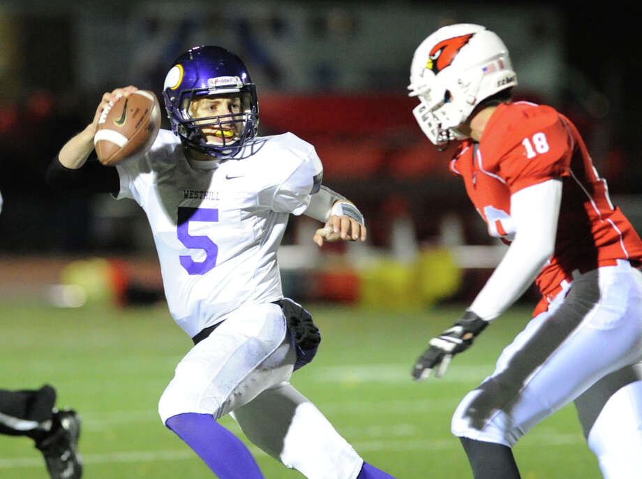 At left, Westhill quarterback Ryan Coppola (# 5) attempts to get away from Jon Fischer (# 18) of Greenwich during the high school football game between Greenwich High School and Westhill High School at Greenwich, Friday, Nov. 8, 2013. Photo: Bob Luckey / Greenwich Time