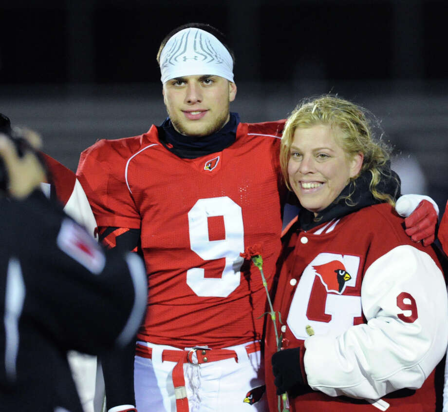 At left, Thomas Martins (# 9) of Greenwich and his mother, Patricia, prior to the start of the high school football game between Greenwich High School and Westhill High School at Greenwich, Friday, Nov. 8, 2013. Photo: Bob Luckey / Greenwich Time