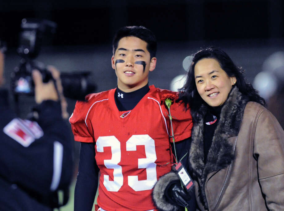 At left, Sangjoon Chung (# 33) of Greenwich with his mother, Suna, prior to the start of the High school football game between Greenwich High School and Westhill High School at Greenwich, Friday, Nov. 8, 2013. Photo: Bob Luckey / Greenwich Time