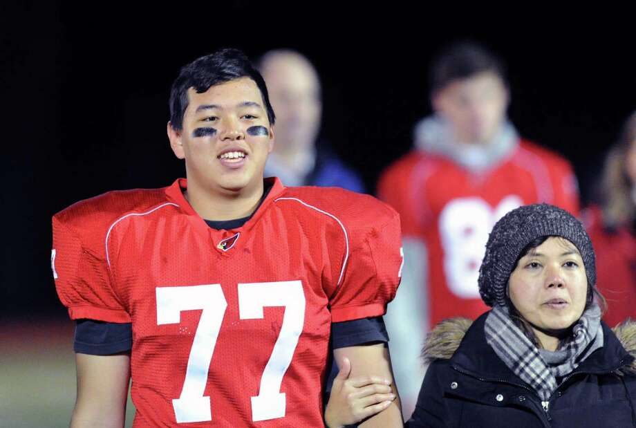 At left, Ratchanon Rattanavaraporn (# 77) of Greenwich with his mother, Monchaya, prior to the start of the high school football game between Greenwich High School and Westhill High School at Greenwich, Friday, Nov. 8, 2013. Photo: Bob Luckey / Greenwich Time