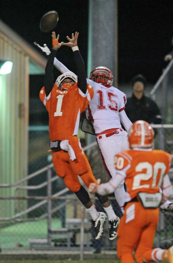 Bridge City's Malcolm Busby (15) and Orangefield's Carmichael Wiley (1) go up for a pass during first half action.