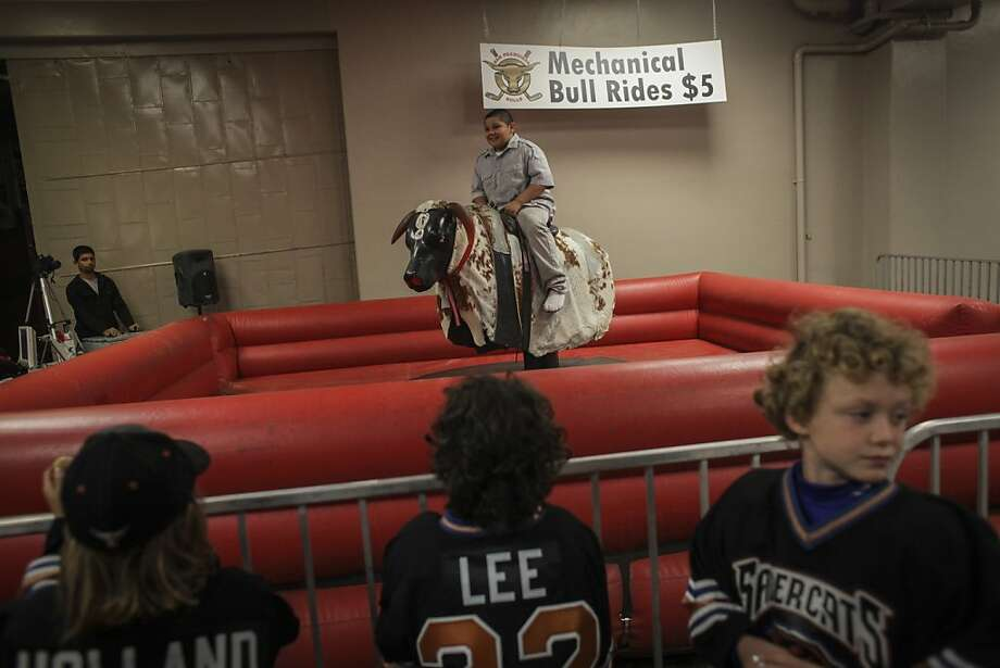 Joshua Rojas, 9 years old from San Francisco, rides a mechanical bull during the San Francisco Bulls opening night match against the Bakersfield Condors at Cow Palace in San Francisco on November 8th 2013. Photo: Sam Wolson, Special To The Chronicle