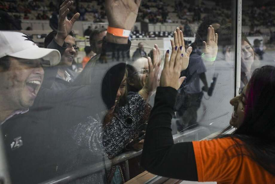 Nicole Villagran, the on the ice announcer for the Bulls, bangs on the glass with fans during the San Francisco Bulls opening night match against the Bakersfield Condors at Cow Palace in San Francisco on November 8th 2013. Photo: Sam Wolson, Special To The Chronicle