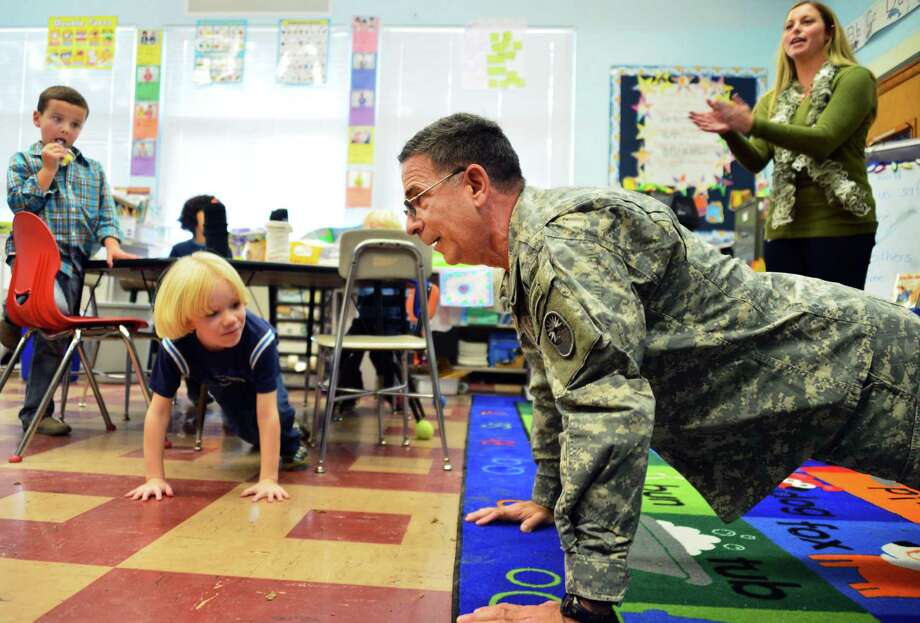 US Army Col. Norberto Cintron, of Port St. Lucy, Fla., teaches Heather Giglello's, at right, first graders the army way to do a push up as he visits his granddaughter's class during Bell Top Elementary School's Veterans Day Recognition Celebration Friday Nov. 8, 2013, in Troy, NY.  (John Carl D'Annibale / Times Union) Photo: John Carl D'Annibale / 00024571A