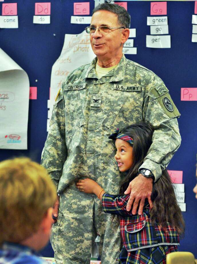 Seven-year-old Salila Cintron hugs her grandfather, US Army Col. Norberto Cintron, of Port St. Lucy, Fla.,  teaches Heather Giglello's, at right, as he visits her class during Bell Top Elementary School's Veterans Day Recognition Celebration Friday Nov. 8, 2013, in Troy, NY.  (John Carl D'Annibale / Times Union) Photo: John Carl D'Annibale / 00024571A