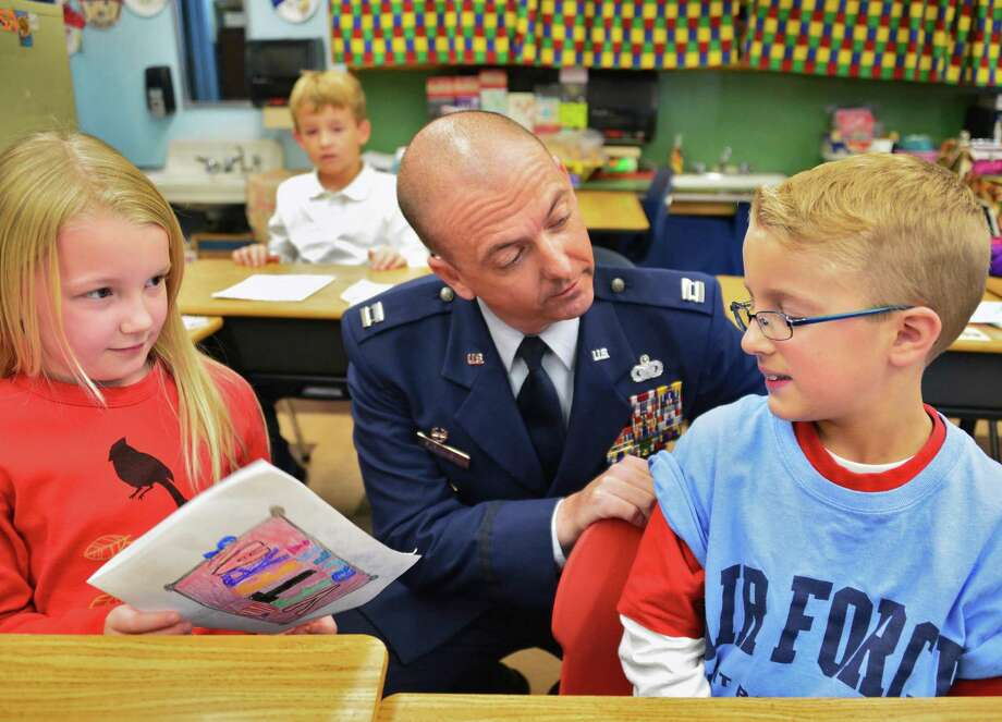 US Air Force Capt. William Furmanski, commander of the 109th Security Forces Sqadron in Scotia, visits with his son Andrew Furmanski, 7, and Andrew's classmate Kaiya Hibbs-Sanger, 7, during Bell Top Elementary School's Veterans Day Recognition Celebrations Friday Nov. 8, 2013, in Troy, NY.  (John Carl D'Annibale / Times Union) Photo: John Carl D'Annibale / 00024571A