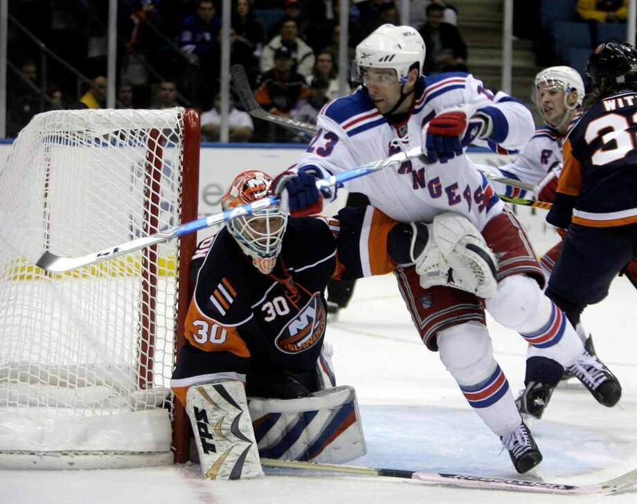 New York Islanders goalie Dwayne Roloson, left, keeps an arm on New York Rangers' Chris Drury during the third period of the NHL hockey game Wednesday, Oct. 28, 2009, in Uniondale, N.Y.   The Islanders beat the Rangers, 3-1.  (AP Photo/Seth Wenig) Photo: Seth Wenig, AP / AP