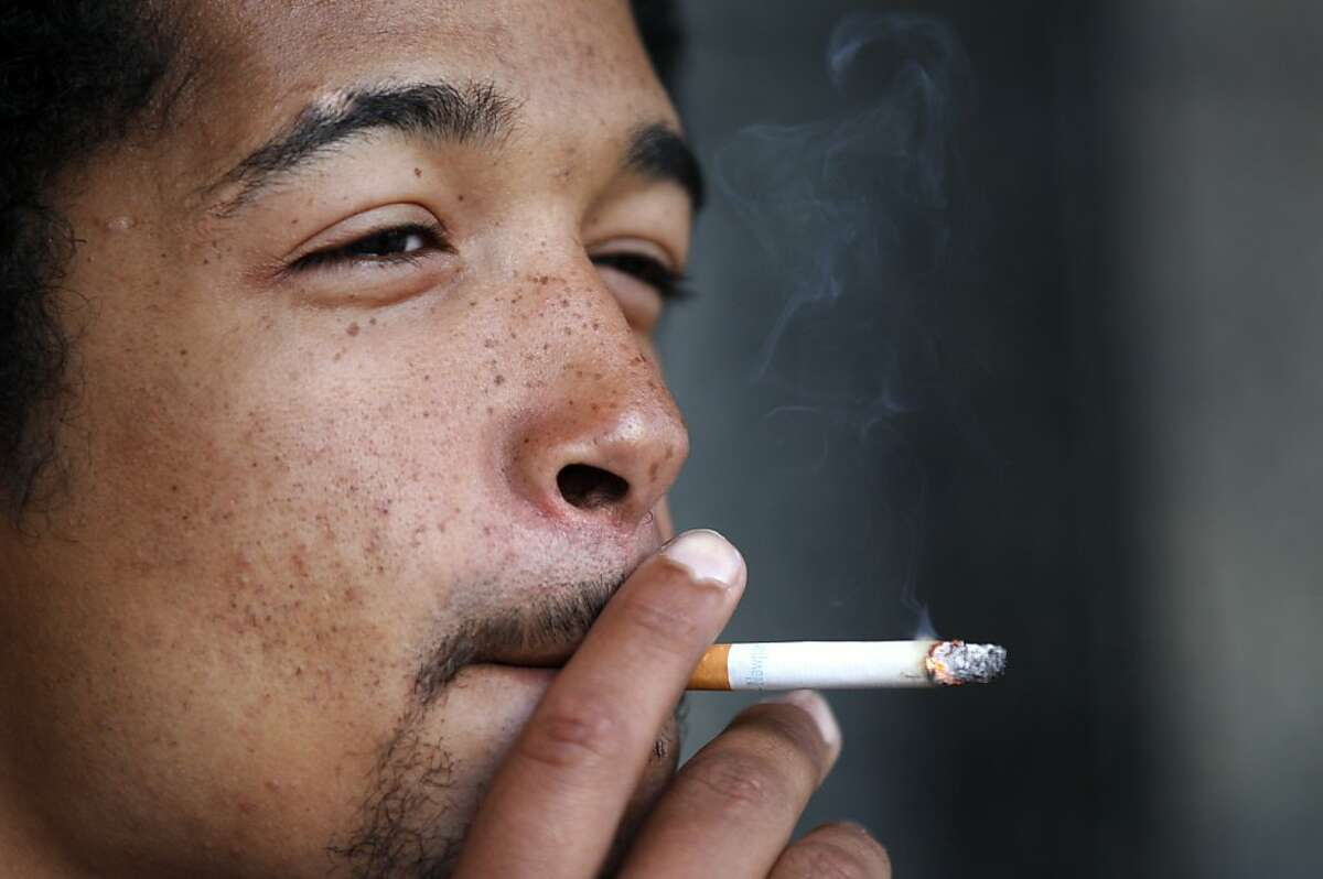 Timothy Lewis, 22, smokes a cigarette off of Market Street November 7, 2013 in downtown San Francisco, Calif. Those who wish to increase the tax on cigarettes to pay for cancer research are collecting signatures again after a narrow defeat at the ballot box last year.