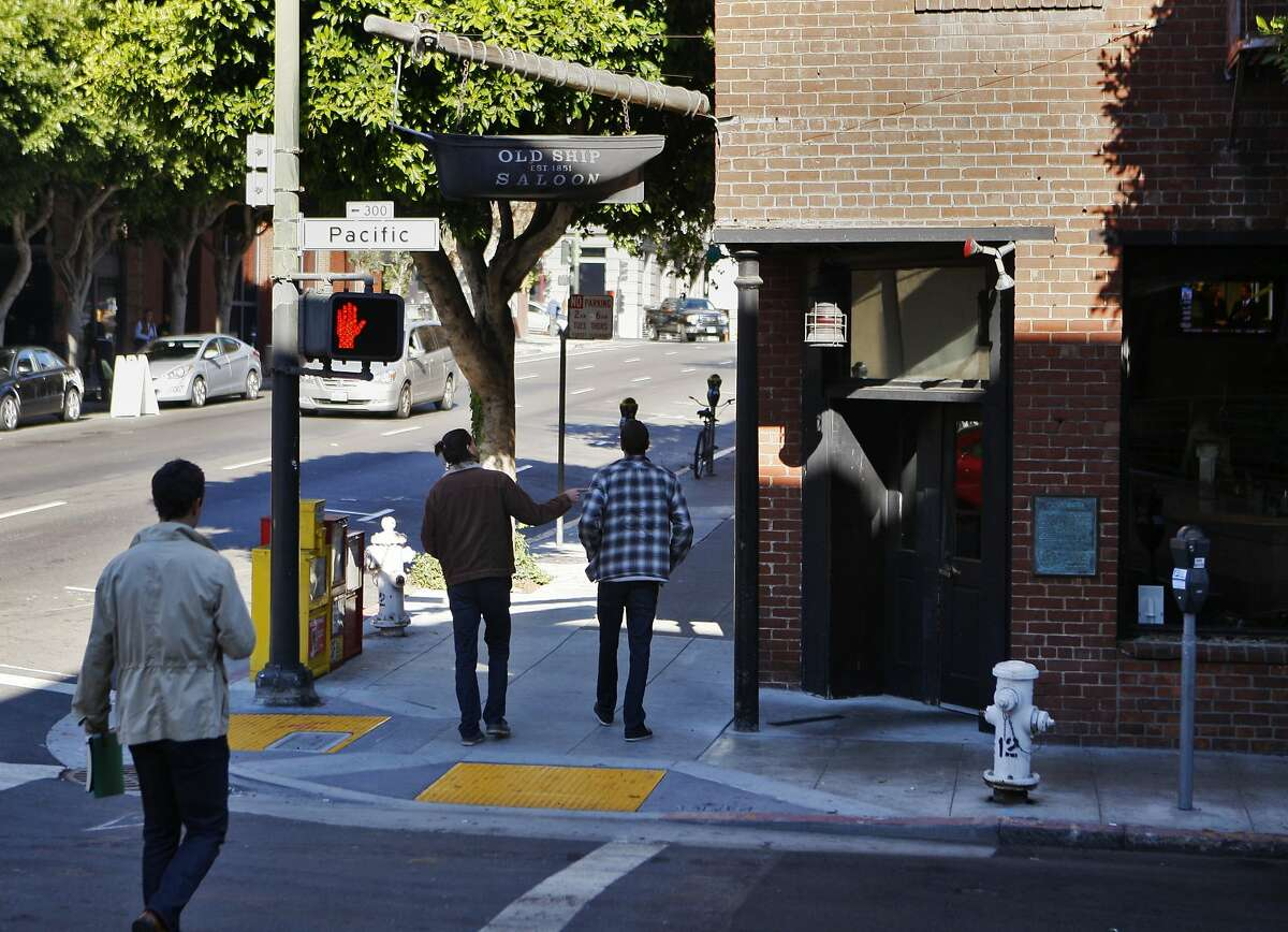 Pedestrians pass by the Old Ship Saloon on the corner of Battery and Pacific in San Francisco, Calif. on Friday, Nov. 8, 2013.