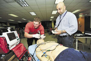 San Jacinto College EMT instructor Ali Shah, right, helps Navy veteran and EMT student Erik Pierce, left, with a class project. San Jacinto College is working to maximize academic credits for veterans, especially those interested in allied health fields.