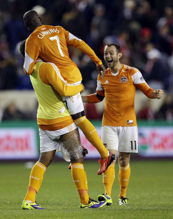 Dynamo players celebrate a game-winning goal by Omar Cummings against the New York Red Bulls. Photo: Julio Cortez, Associated Press