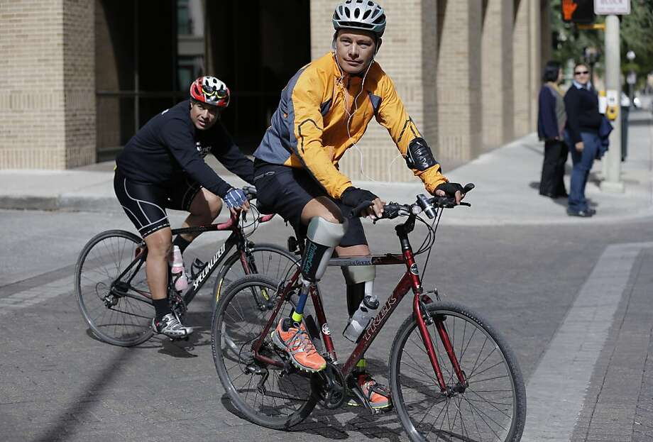 Cyclist Carlos Gutierrez, right, a double amputee, rides his bike, Thursday, Nov. 7, 2013, in San Antonio. Gutierrez, a Mexican asylum seeker who fled to the U.S. after extortionists cut his legs off for not paying the extortion fees, is riding his bike from El Paso, Texas to Austin, Texas, to raise awareness on the situation of political asylum seekers.  (AP Photo/Eric Gay) Photo: Eric Gay, Associated Press