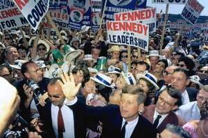 "Sen. John F. Kennedy made his way through a crowd of supporters and journalists in Los Angeles on July 9, 1960, at the Democratic National Convention. Kennedy's election in 1960 helped to bolster the spirits of many Americans from ""the greatest generation."""