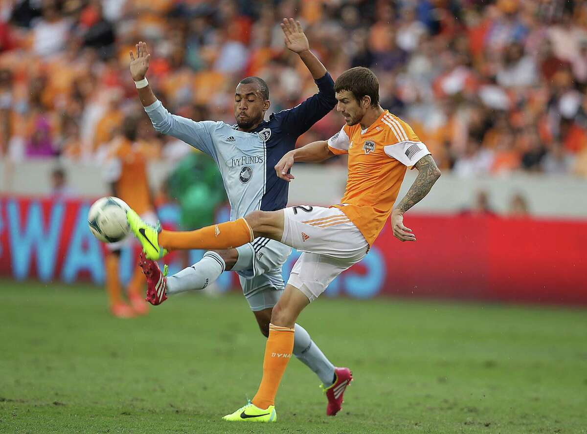 Sporting KC forward Teal Bunbury left, and Houston Dynamo defender Eric Brunner right, during the first half of the MLS Eastern Conference Final game at BBVA Compass Stadium Saturday, Nov. 9, 2013, in Houston.