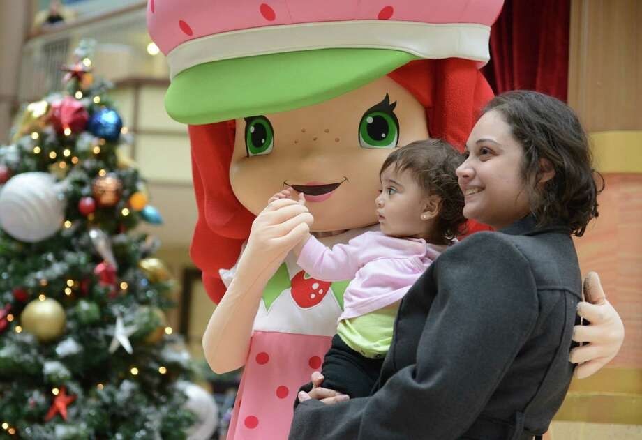 Silvana Abraham, of Woodbury, and her daughter Emily Abraham, 1, get a photo with Strawberry Shortcake, afteran interactive childrens show welcoming Santa Claus at Danbury Fair in Danbury, Conn. on Saturday, Nov. 9, 2013.  Santa and Stawberry Shortcake stayed after the show for a meet-and-greet with photos. Photo: Tyler Sizemore / The News-Times
