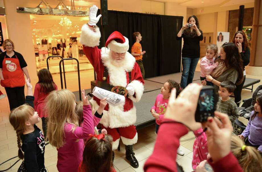 After an interactive show featuring Strawberry Shortcake, Santa Claus is welcomed to the Danbury Fair in Danbury, Conn. on Saturday, Nov. 9, 2013.  Santa and Stawberry Shortcake stayed after the show for a meet-and-greet with photos. Photo: Tyler Sizemore / The News-Times