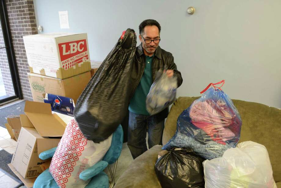 Herbert Cledera, owner of H&K Filipino Variety Store, looks through bags of donations of items to be sent to help the victims of the typhoon in the Philippines at his store in Danbury, Conn. on Saturday, Nov. 9, 2013.  Donations of clothing, blankets, canned food and toiletries will be accepted until Nov. 21. Photo: Tyler Sizemore / The News-Times
