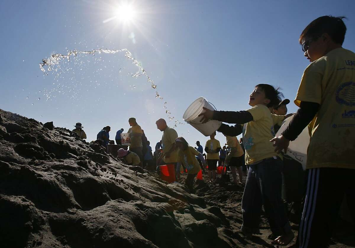 A student from Robert Louis Stevenson Elementary tosses water onto his team pile of sand during the Leap Sand Castle Contest at Ocean Beach in San Francisco, Calif. on Saturday, Nov. 9, 2013.