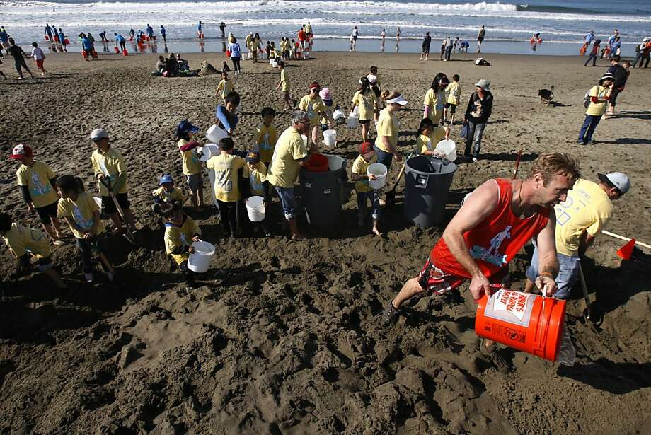 Kevin Firenze of Dome Contstruction (right) dumps a bucket of water on his teams pile of sand during the Leap Sand Castle Contest at Ocean Beach in San Francisco, Calif. on Saturday, Nov. 9, 2013. Photo: Raphael Kluzniok, The Chronicle