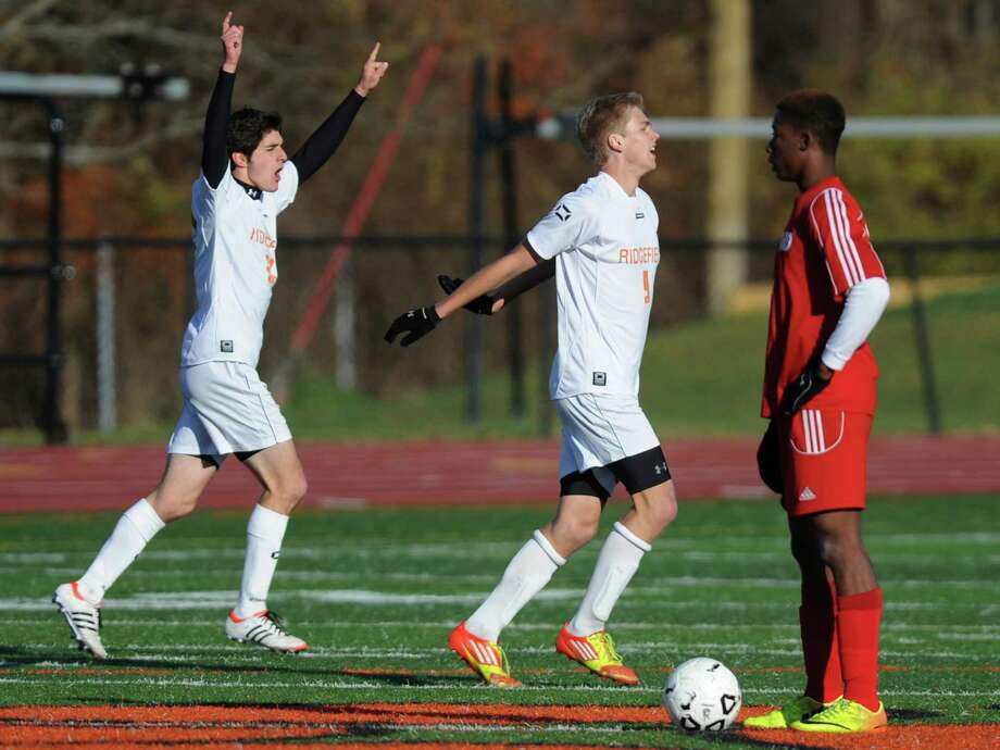 Ridgefield's Ryan Casolo, left, and Adam Findlay celebrates a second-half goal in No. 3 Ridgefield's 2-1 win over No. 6 Conard in the Class LL Boys State Soccer Tournament at Ridgefield High School in Ridgefield, Conn. on Saturday, Nov. 9, 2013. Photo: Tyler Sizemore / The News-Times