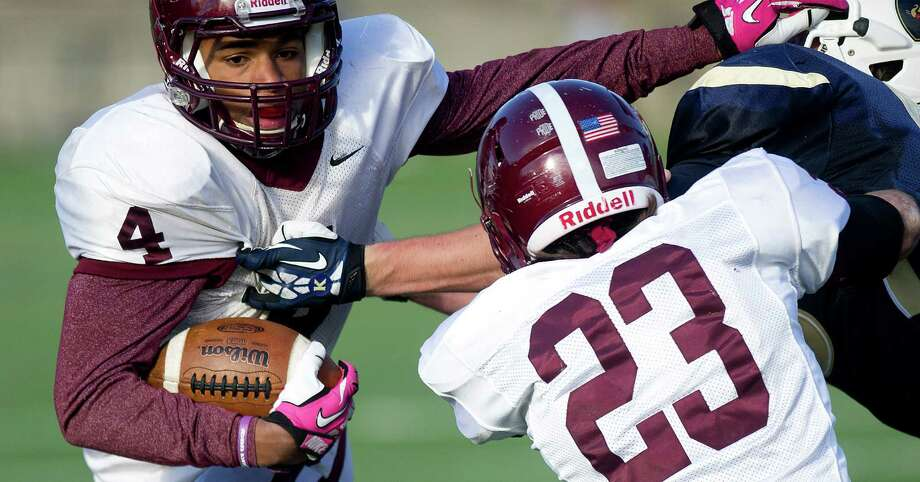 St. Luke's Justin Brown carries the ball during Saturday's football game at King on November 9, 2013. Photo: Lindsay Perry / Stamford Advocate