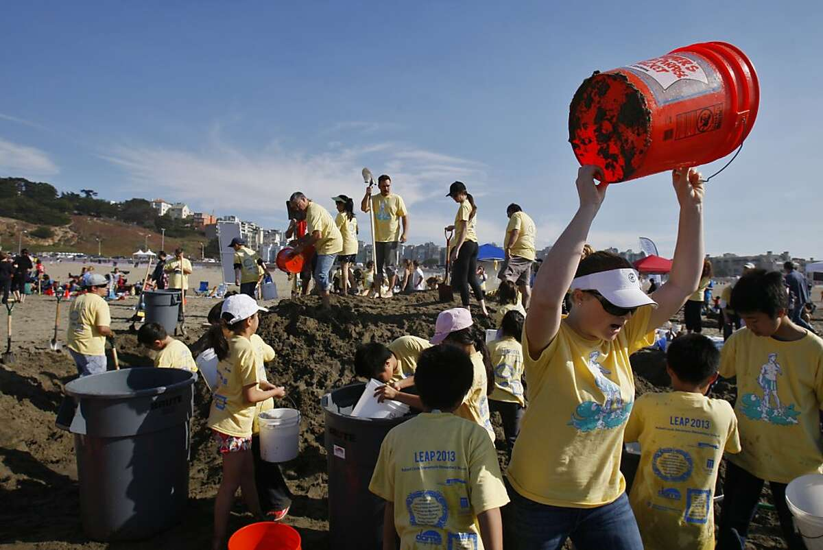 Brynda Kirk rallies her team from Robert Louis Stevenson Elementary to collect more water during the Leap Sand Castle Contest at Ocean Beach in San Francisco, Calif. on Saturday, Nov. 9, 2013.