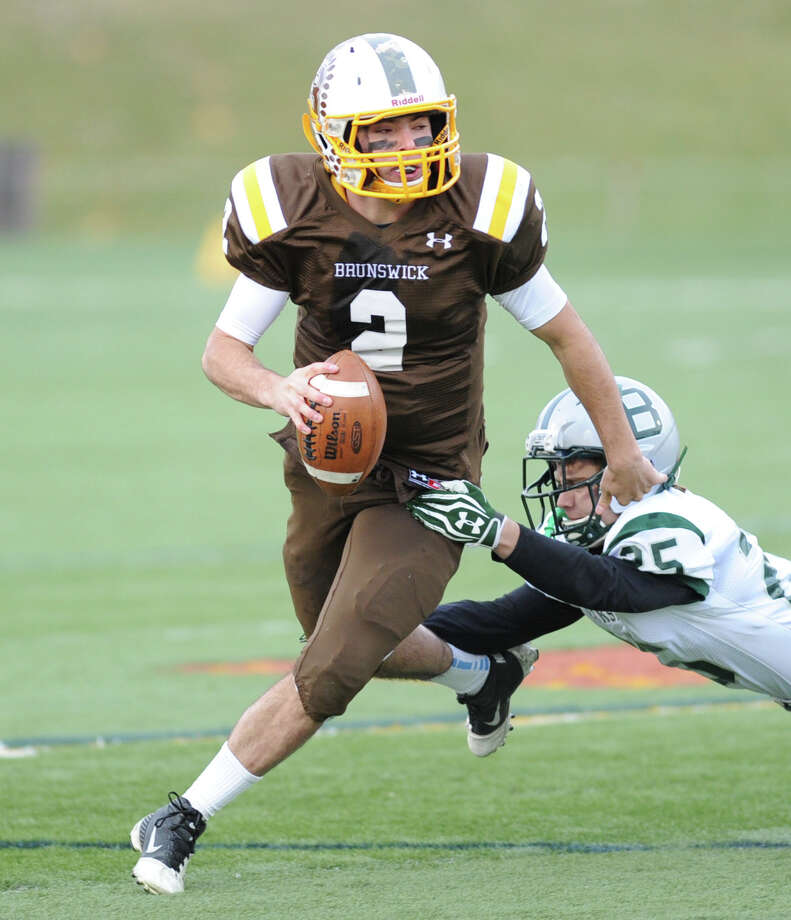 At left, Brunswick quarterback Billy O'Malley (# 2) evades diving Berkshire defender Charlie Erdman (# 25) during the high School football game between Brunswick School and Berkshire School at Brunswick in Greenwich, Nov. 11, 2013. Photo: Bob Luckey / Greenwich Time