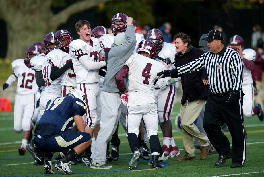 St. Luke's players celebrate after scoring a two-point conversion in overtime to win the game by one point during Saturday's football game at King on November 9, 2013. Photo: Lindsay Perry / Stamford Advocate