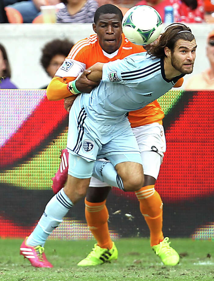 Houston Dynamo defender Kofi Sarkodie left, holds onto Sporting KC midfielder/forward Graham Zusi right during the first half of the MLS Eastern Conference Final game at BBVA Compass Stadium Saturday, Nov. 9, 2013, in Houston. Photo: James Nielsen, Houston Chronicle / © 2013  Houston Chronicle