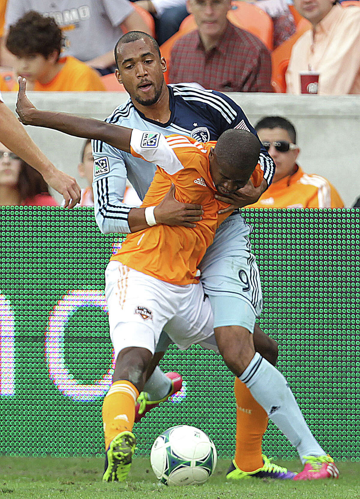 Sporting KC forward Teal Bunbury left, holds onto Houston Dynamo midfielder Boniek Garcia left, during the first half of the MLS Eastern Conference Final game at BBVA Compass Stadium Saturday, Nov. 9, 2013, in Houston.
