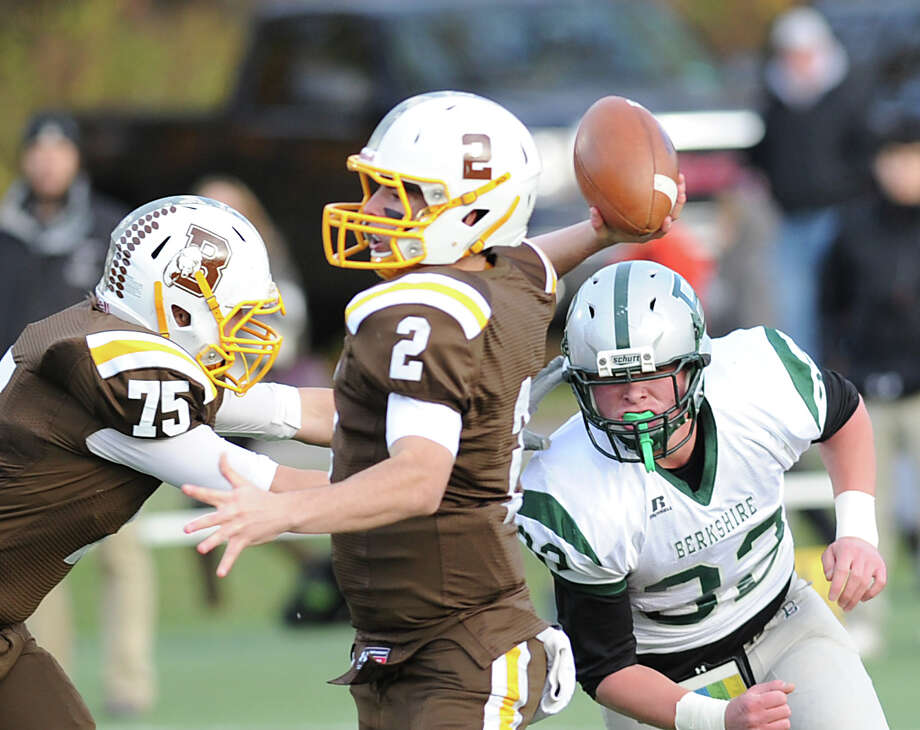 At center, Billy O'Malley, Brunswick quarterback, throws a pass as he gets blocking from teammate, Tommy Adamo (# 75,) while being rushed by Brendan Moloy (# 32) of Berkshire during the High School football game between Brunswick School and Berkshire School at Brunswick in Greenwich, Nov. 11, 2013. Photo: Bob Luckey / Greenwich Time