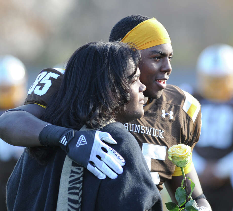 At right, Dylan Wadsworth of Brunswick School presents a yellow rose to his mother, Deelia Wadsworth, as part of a Senior Day tribute prior to the start of the high School football game between Brunswick School and Berkshire School at Brunswick in Greenwich, Nov. 11, 2013. Photo: Bob Luckey / Greenwich Time